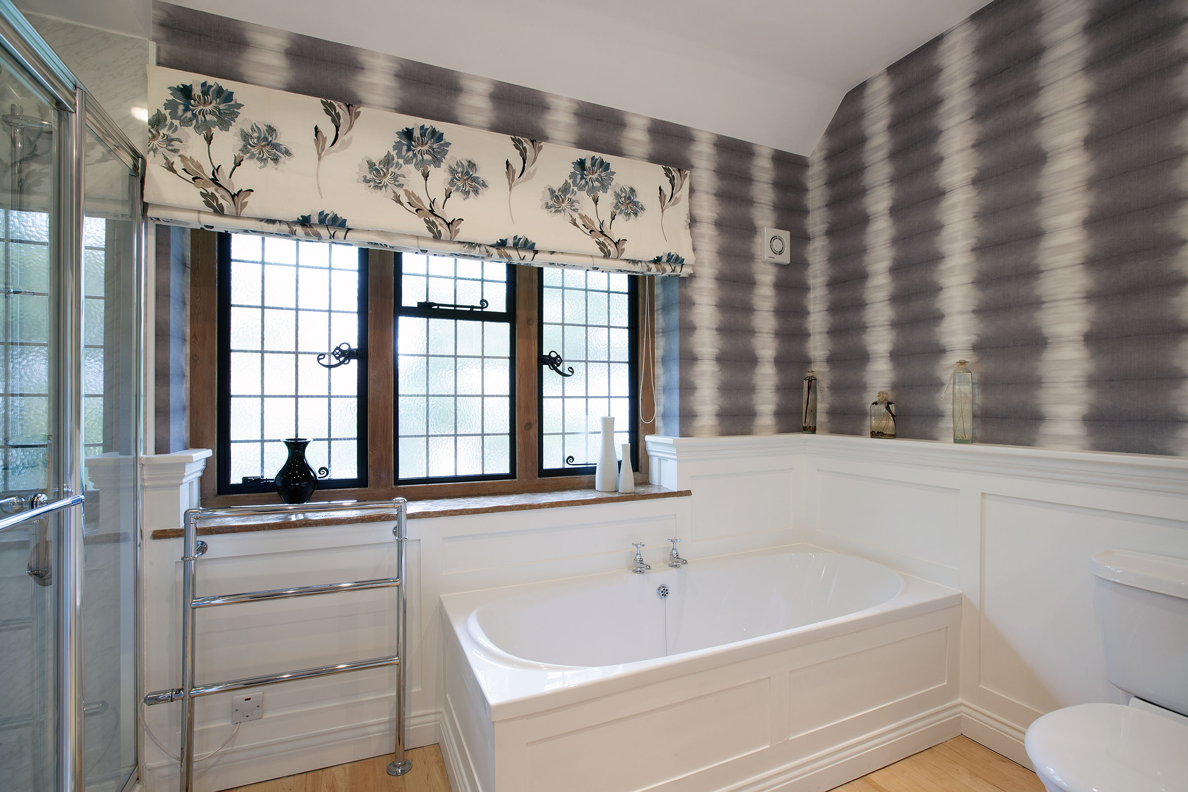 Bathroom with contemporary wallpaper and colour matched roman blind