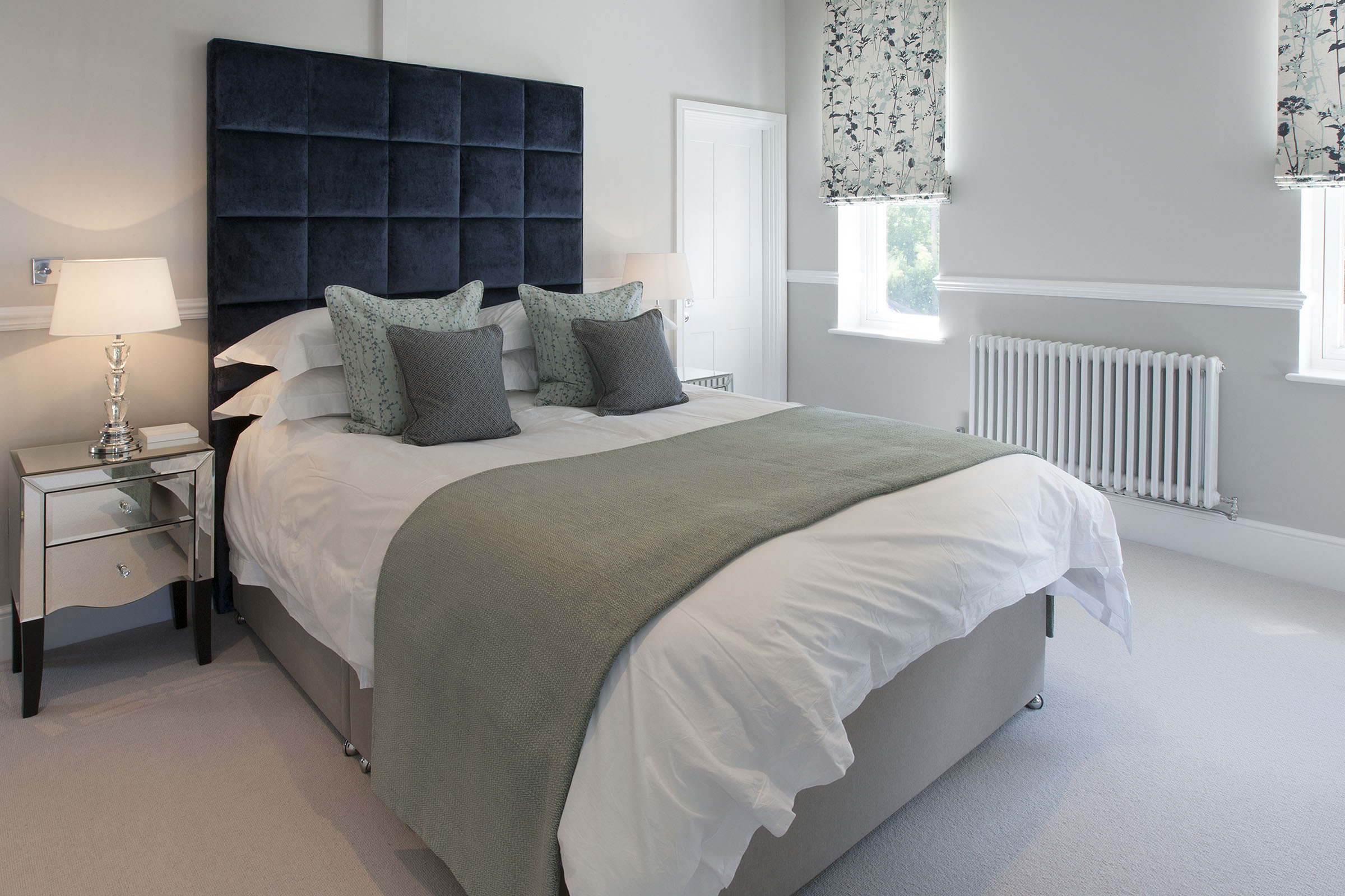Grey and blue bedroom with large cushioned headrest