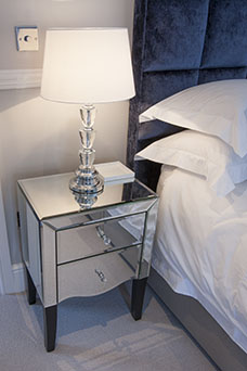 Table lamp on mirrored bedside table