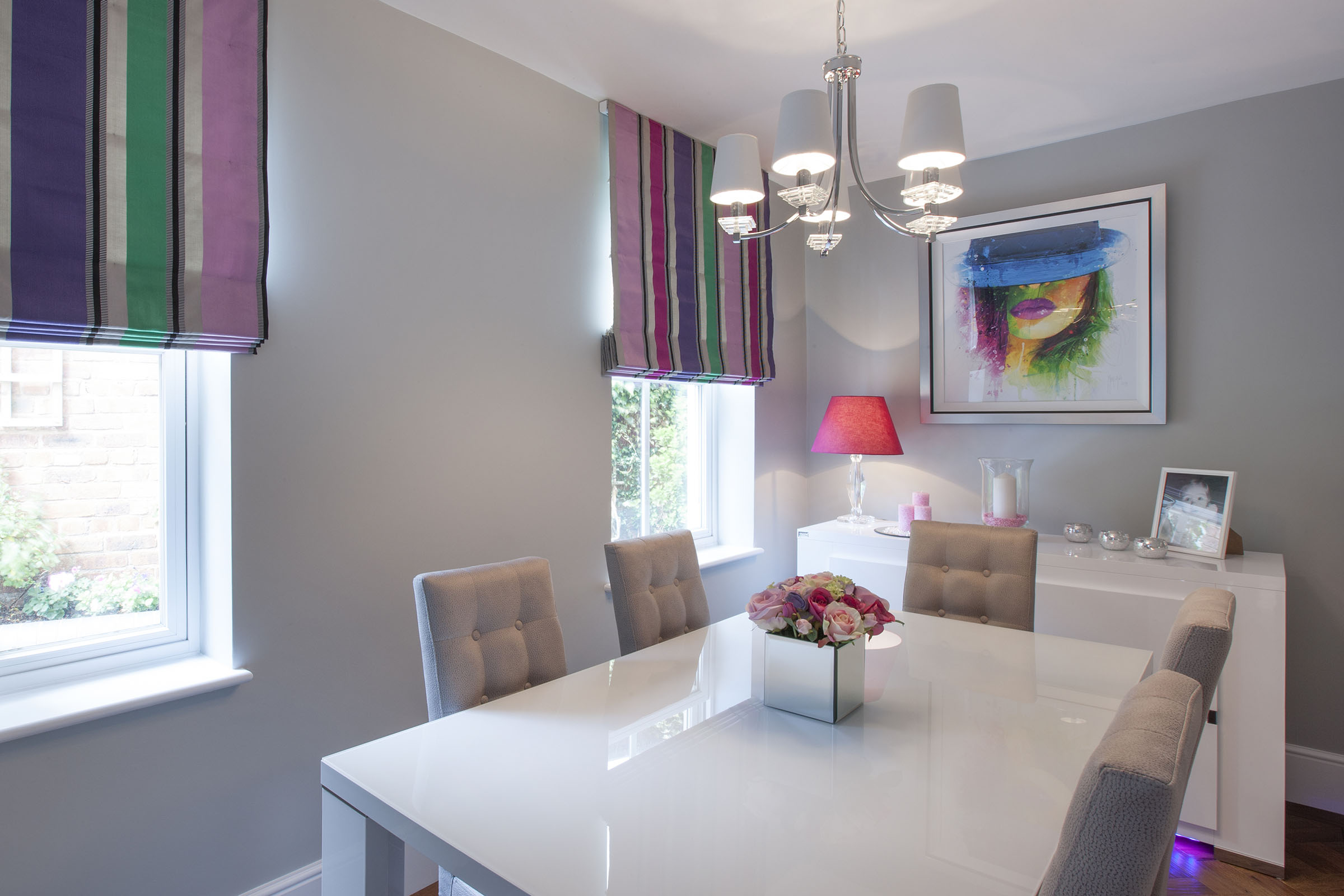 Contemporary light grey and white dining room with multicoloured striped Roman blinds.