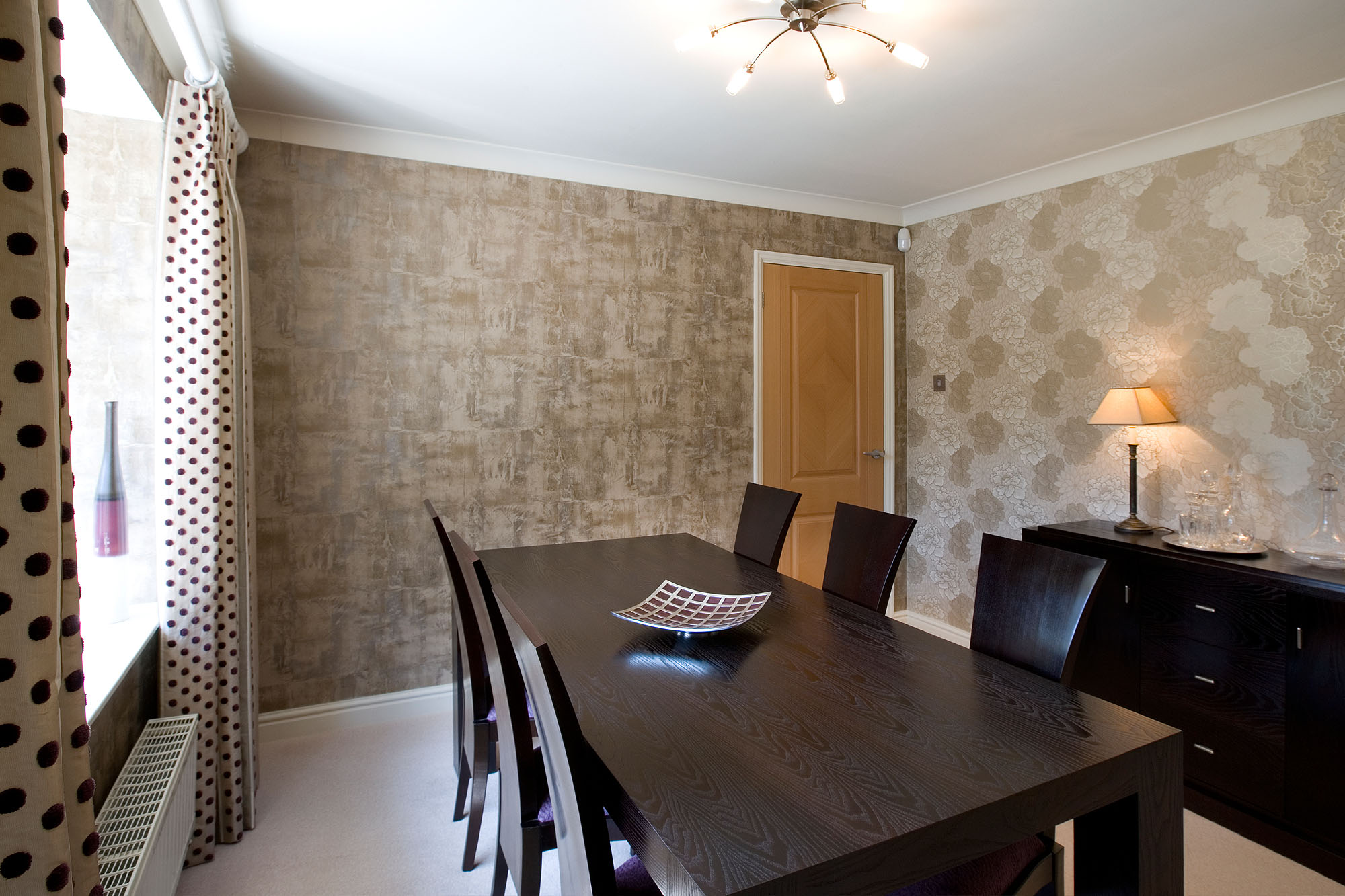 Warm toned dining room with dark brown wood table, contemporary wallpaper and spotted curtains.