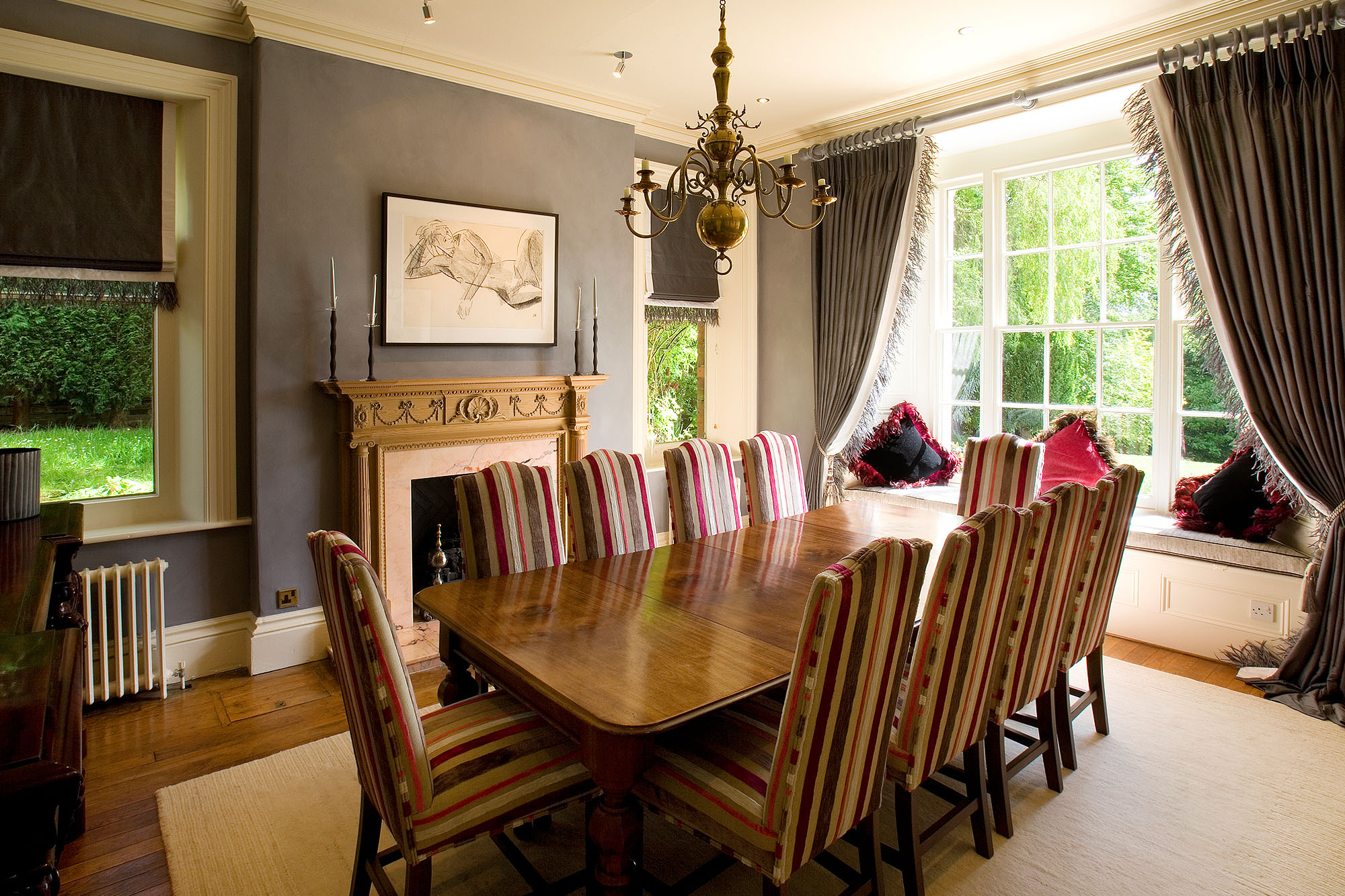 Romantic style dining room in a country residence with wooden dining table, striped dining chairs, wood floor with a plain cream rug, luxury trimmed curtains hung from a curtain pole. Red and grey theme.