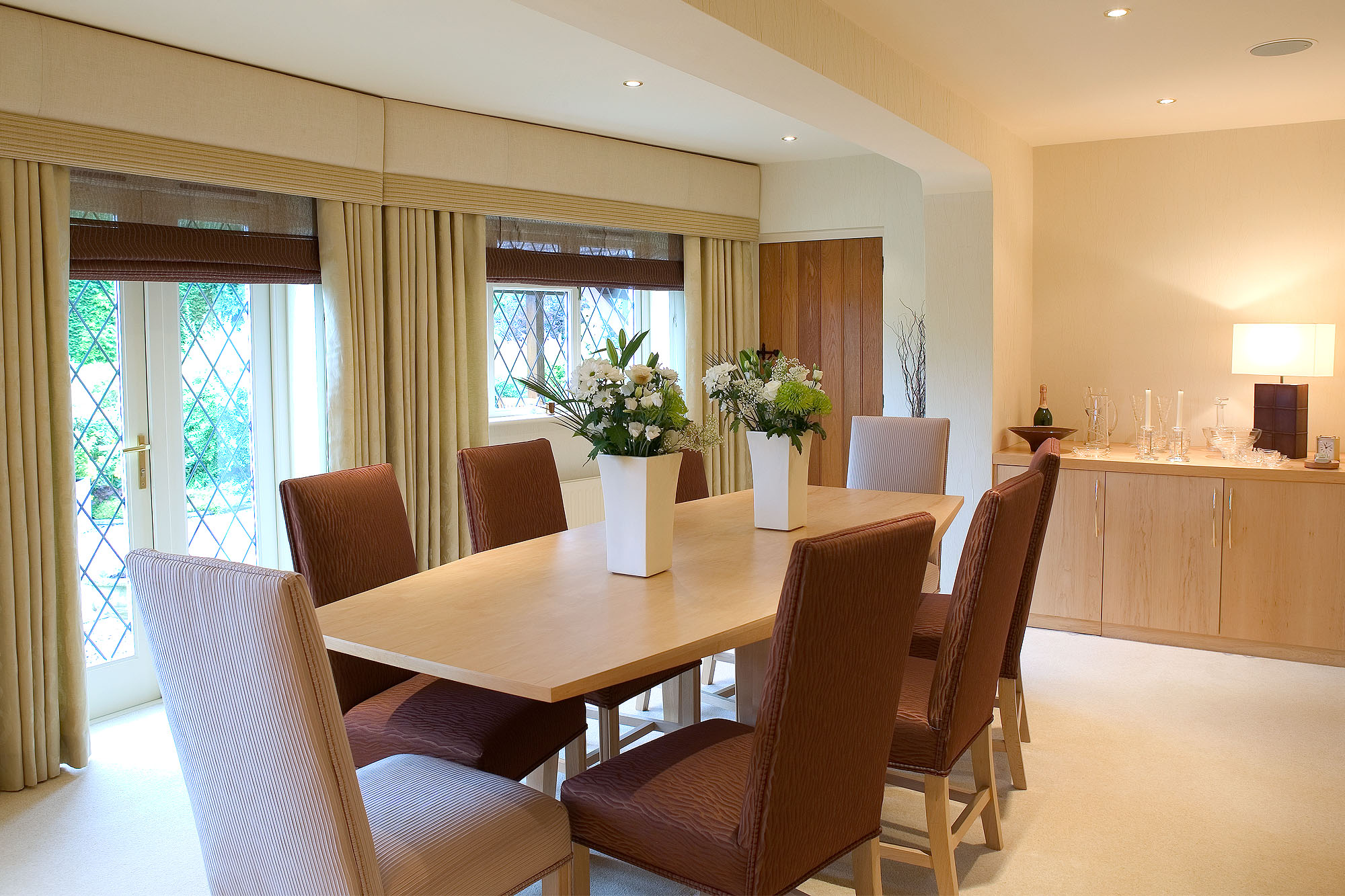 Elegant clean lined dining room with gentle curves, cool tones and lighter wood furniture. Fitted pelmets and contemporary table lamp.