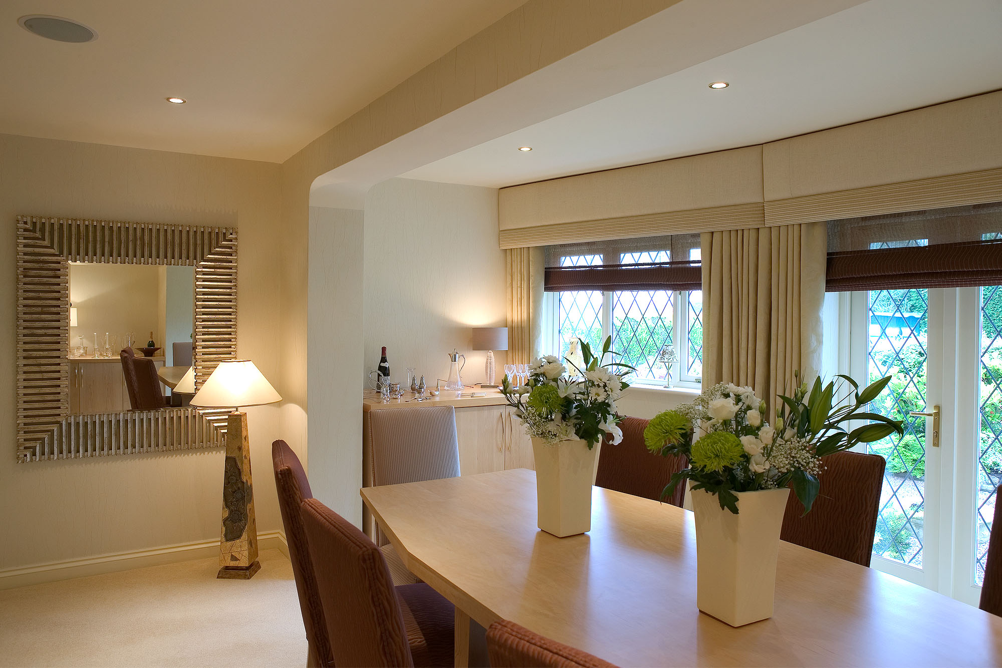 Elegant clean lined dining room with gentle curves, cool tones and lighter wood furniture. Fitted pelmets,contemporary standing lamp and large contemporary mirror.