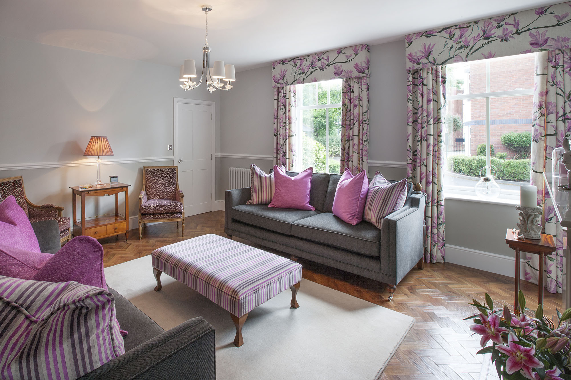 Sitting Room with pink and grey theme showing reupholstered chairs, sofas, a large footstool and wooden side tables.