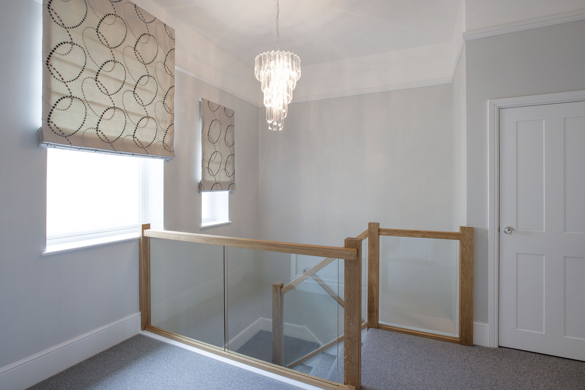 Landing with contemporary grey stair carpet, wood and glass ballustrade and Roman Blinds.