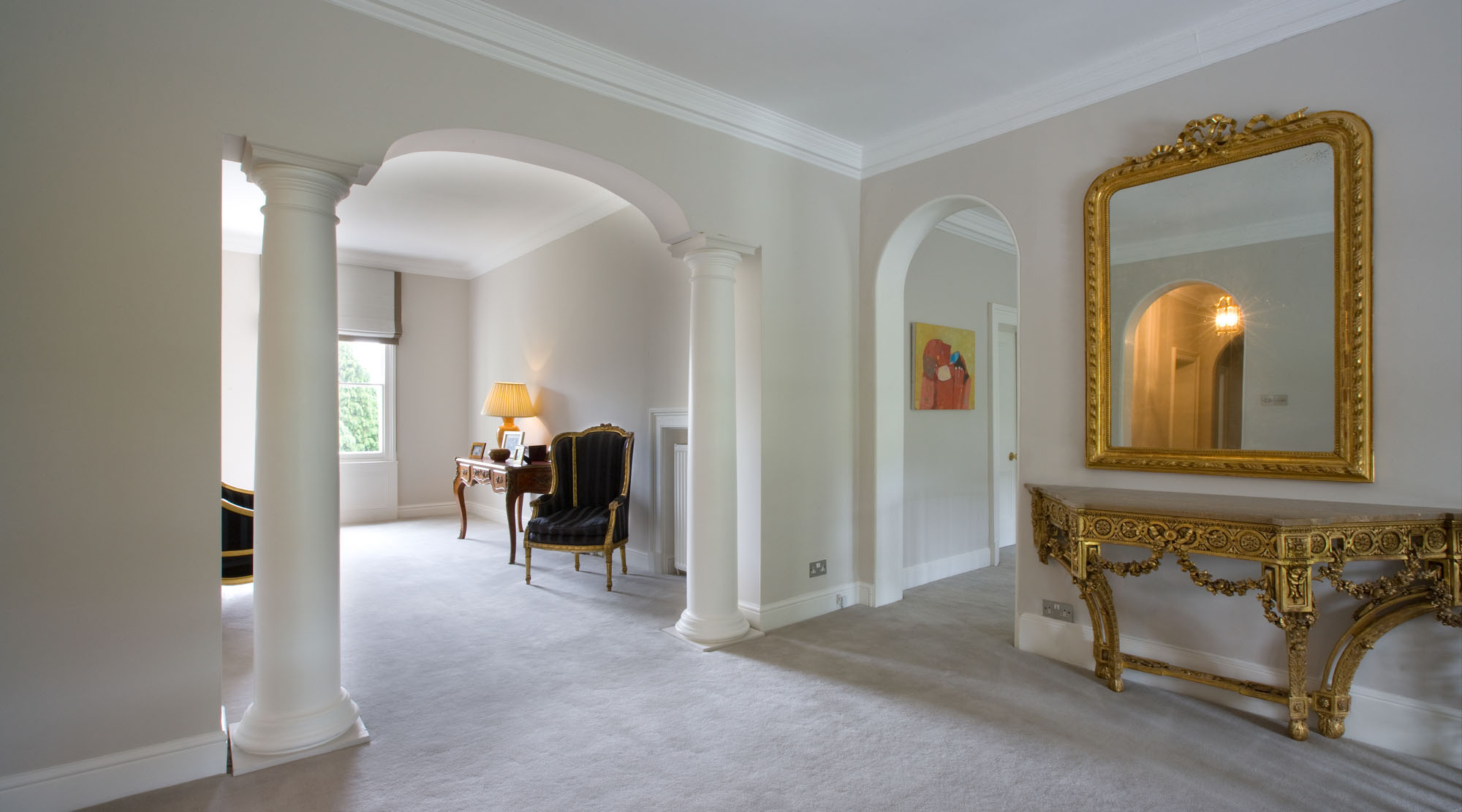 Landing with large gold mirror and marble topped side table.