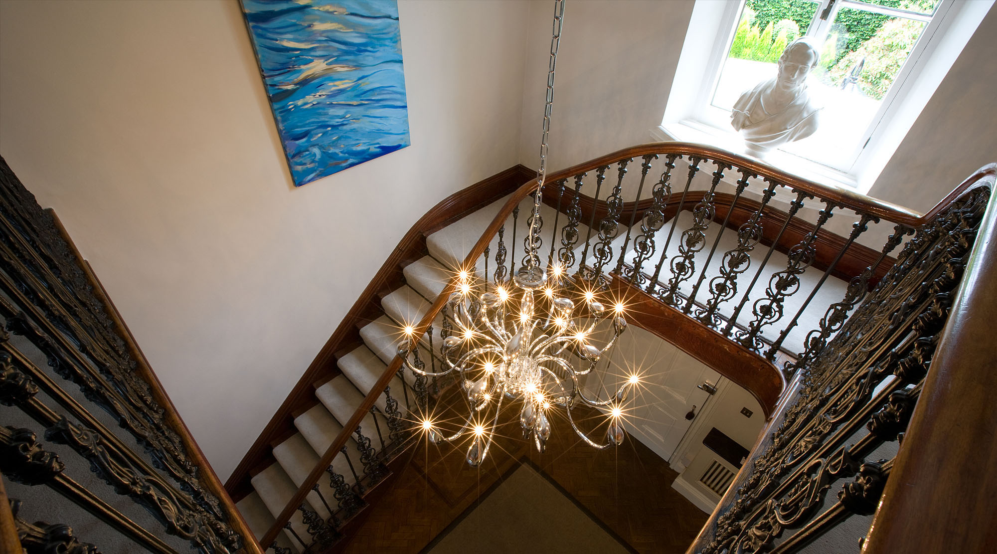 Tradional dark wood returning staircase with large pendant contemporary light fitting.
