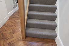 Hall with wooden floor, contemporary grey stair carpet and wood and glass ballustrade.