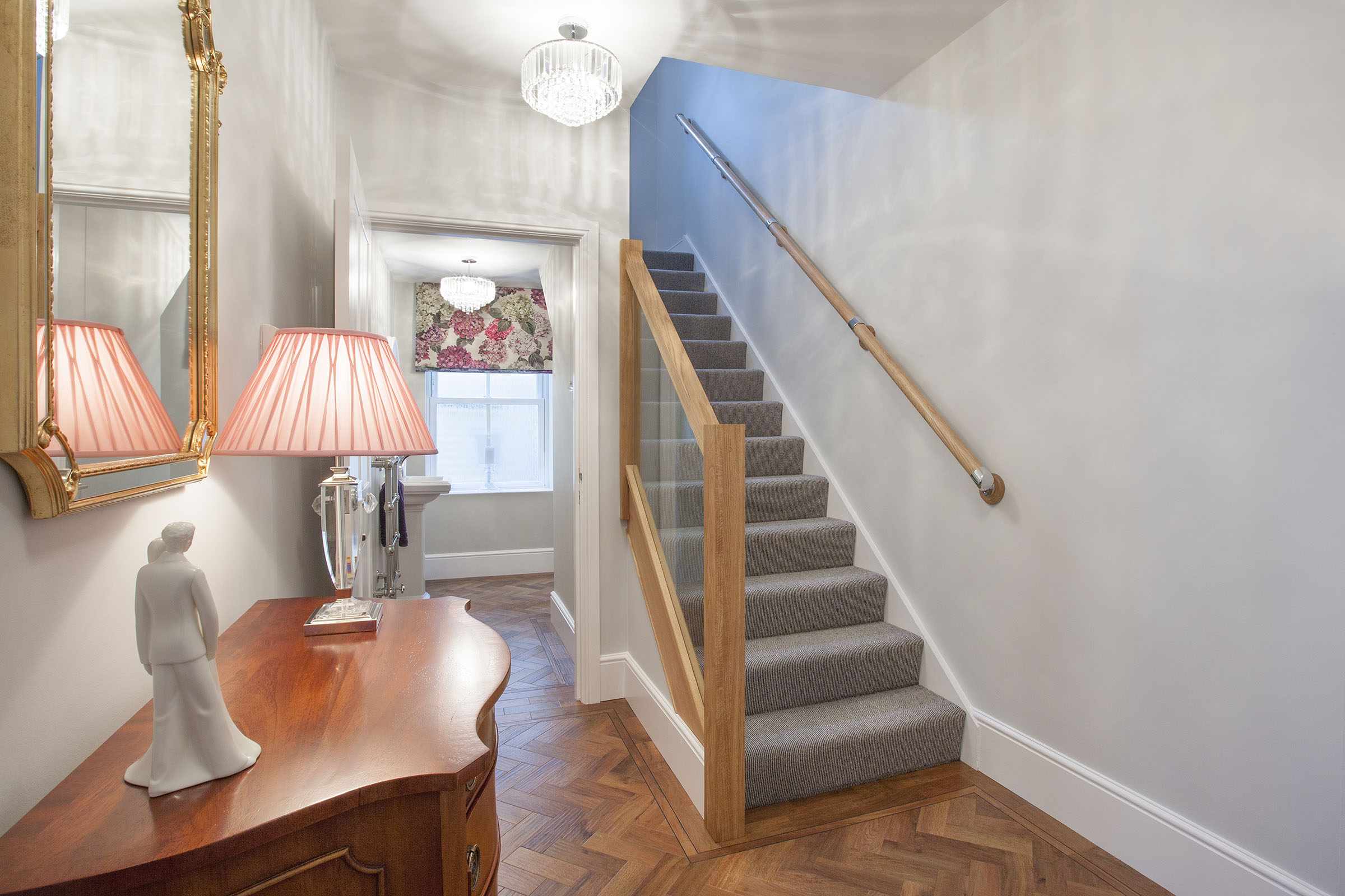 Hall with wooden floor, contemporary grey stair carpet, wood and glass ballustrade, Roman blind.