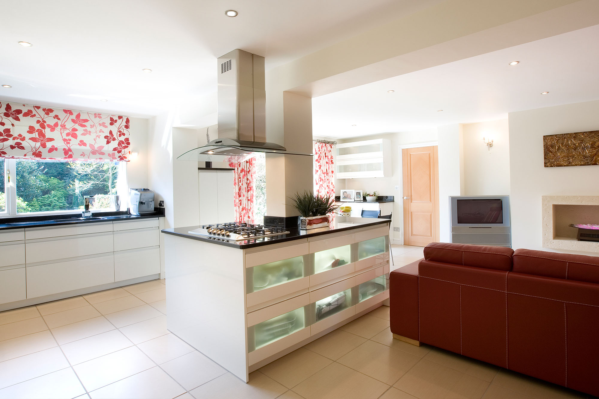 Living Kitchen with red leather sofa and red and white curtains and Roman blinds.