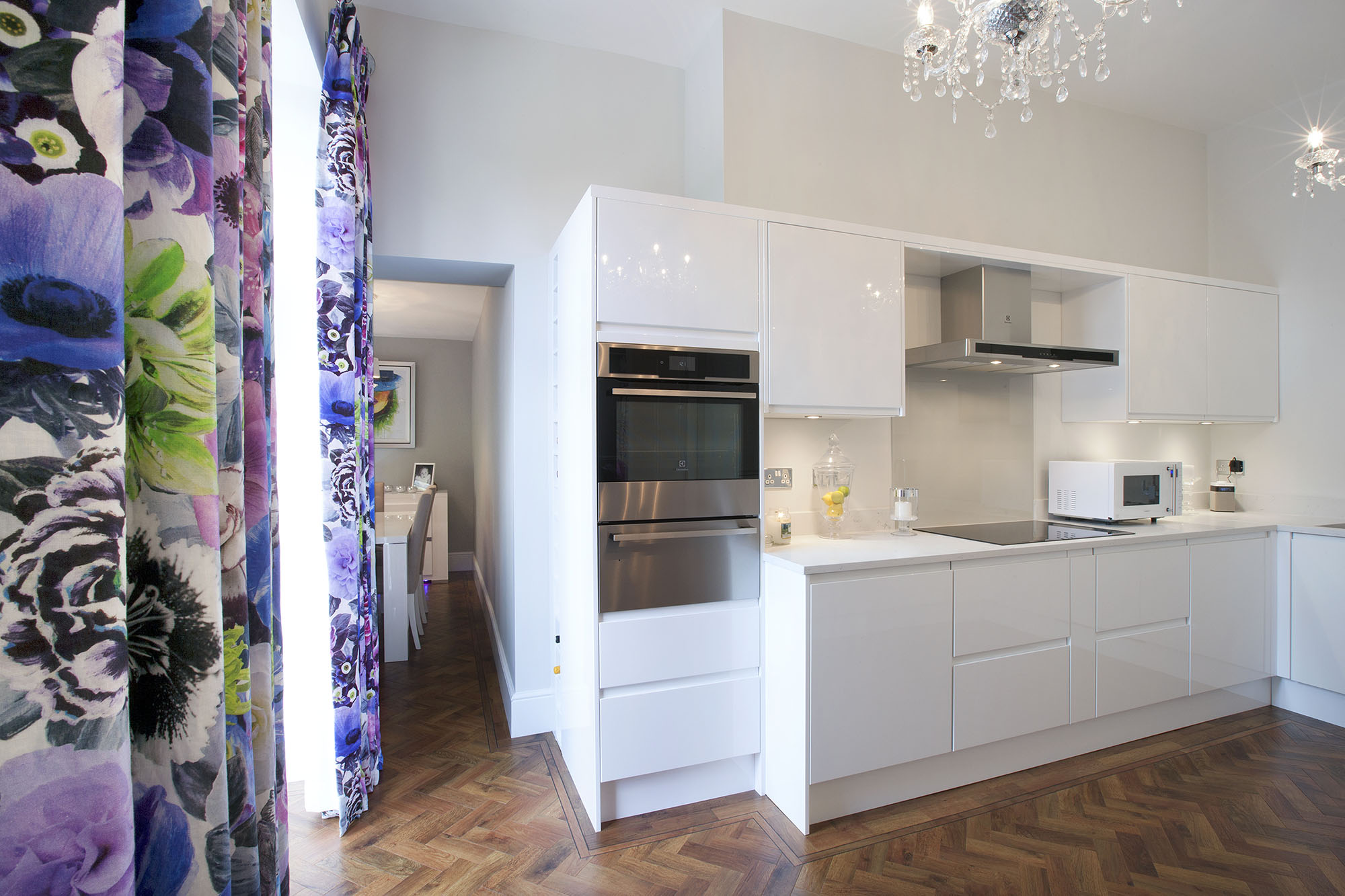 Contemporary white kitchen with wood floor and full length multicoloured curtains.