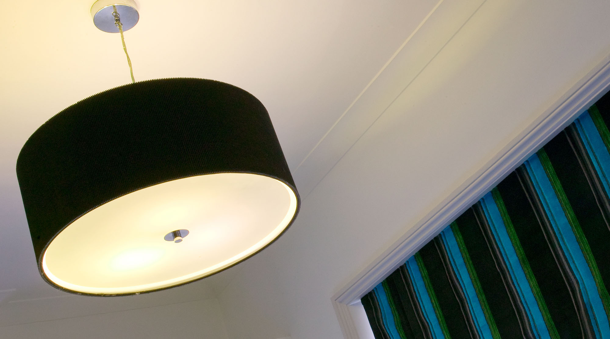 Large round black pendant shade in a bedroom setting.