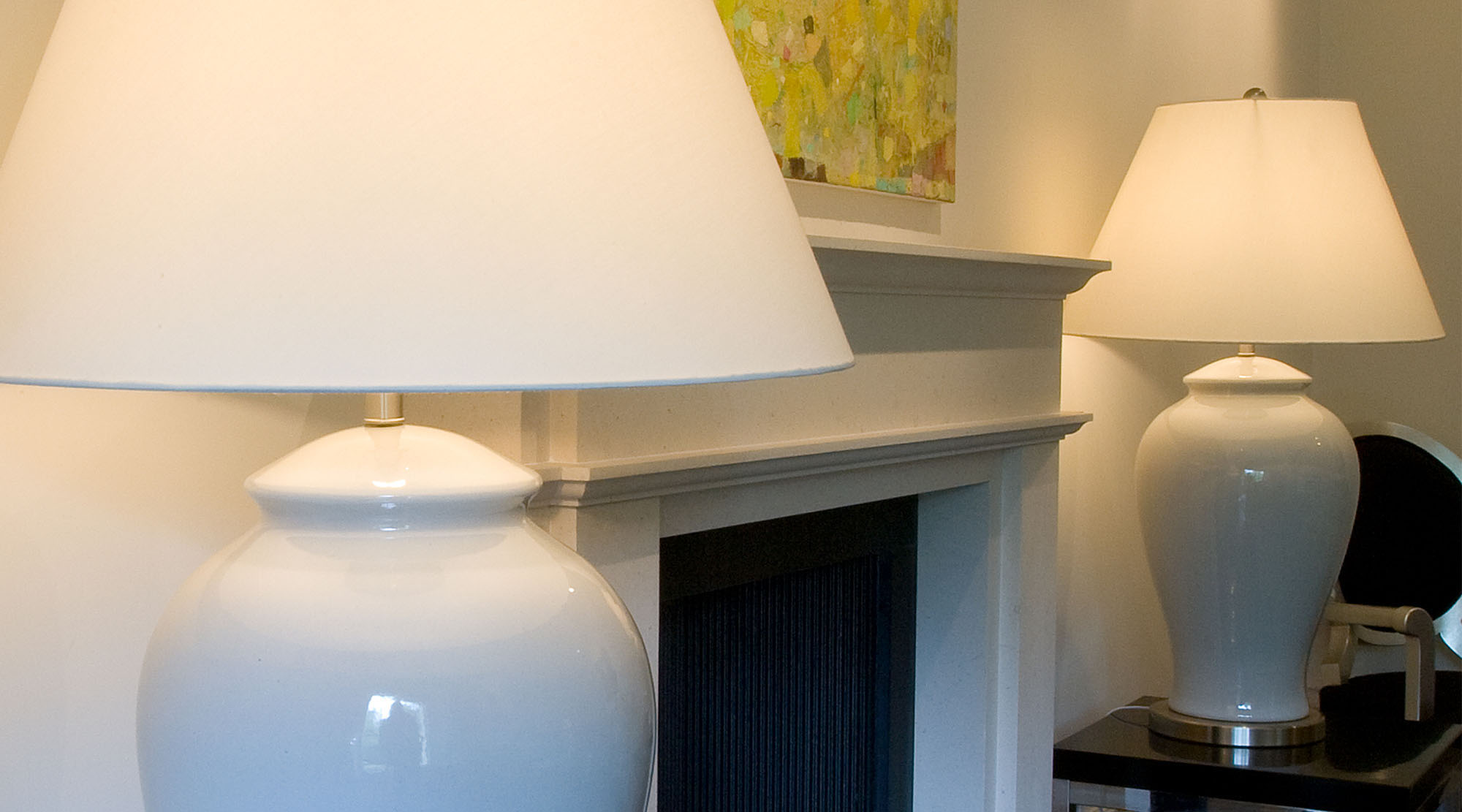 White ceramic table lamps with white shades in a lounge setting.