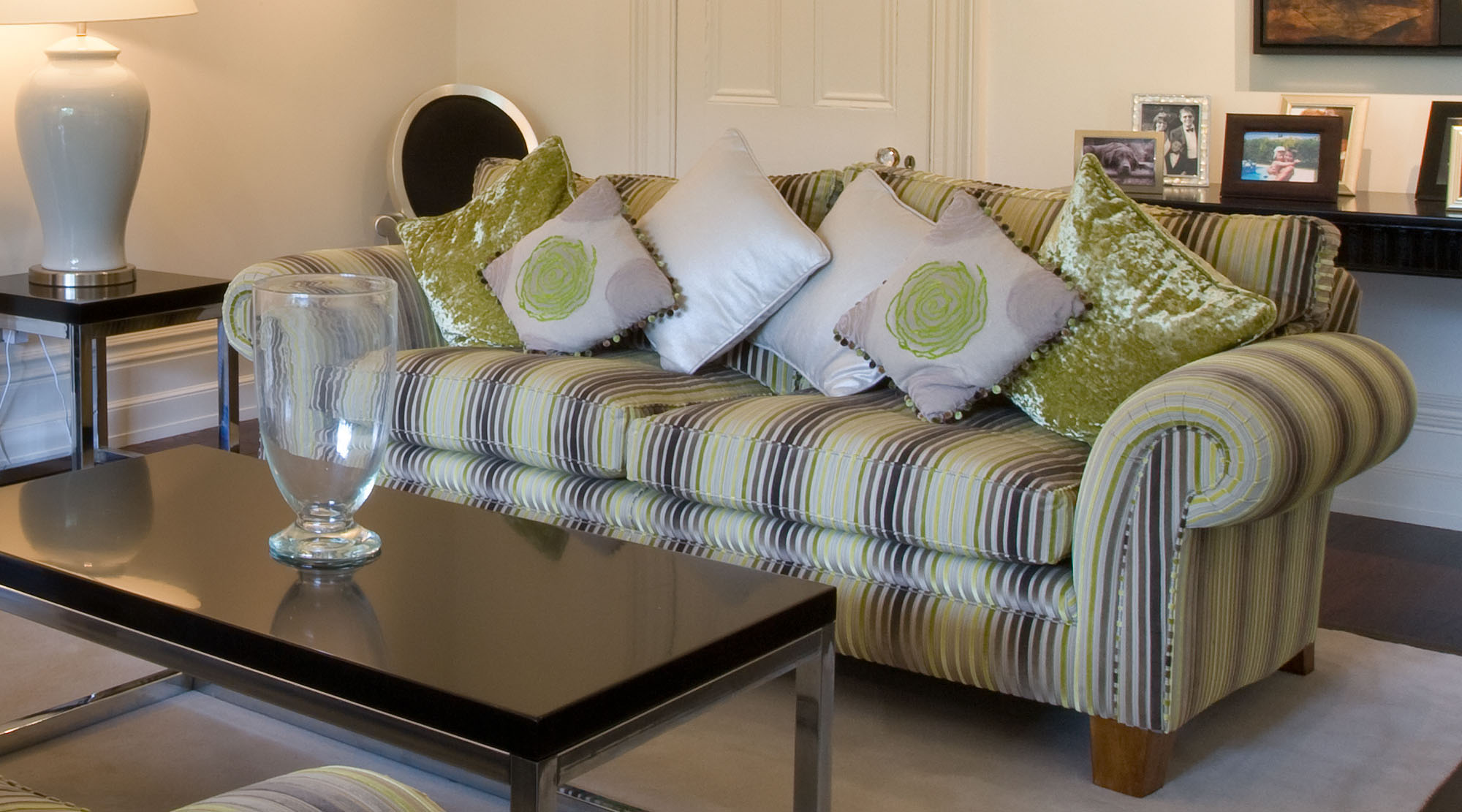 Sitting Room with green and grey themed sofa and luxury trimmed cushions.