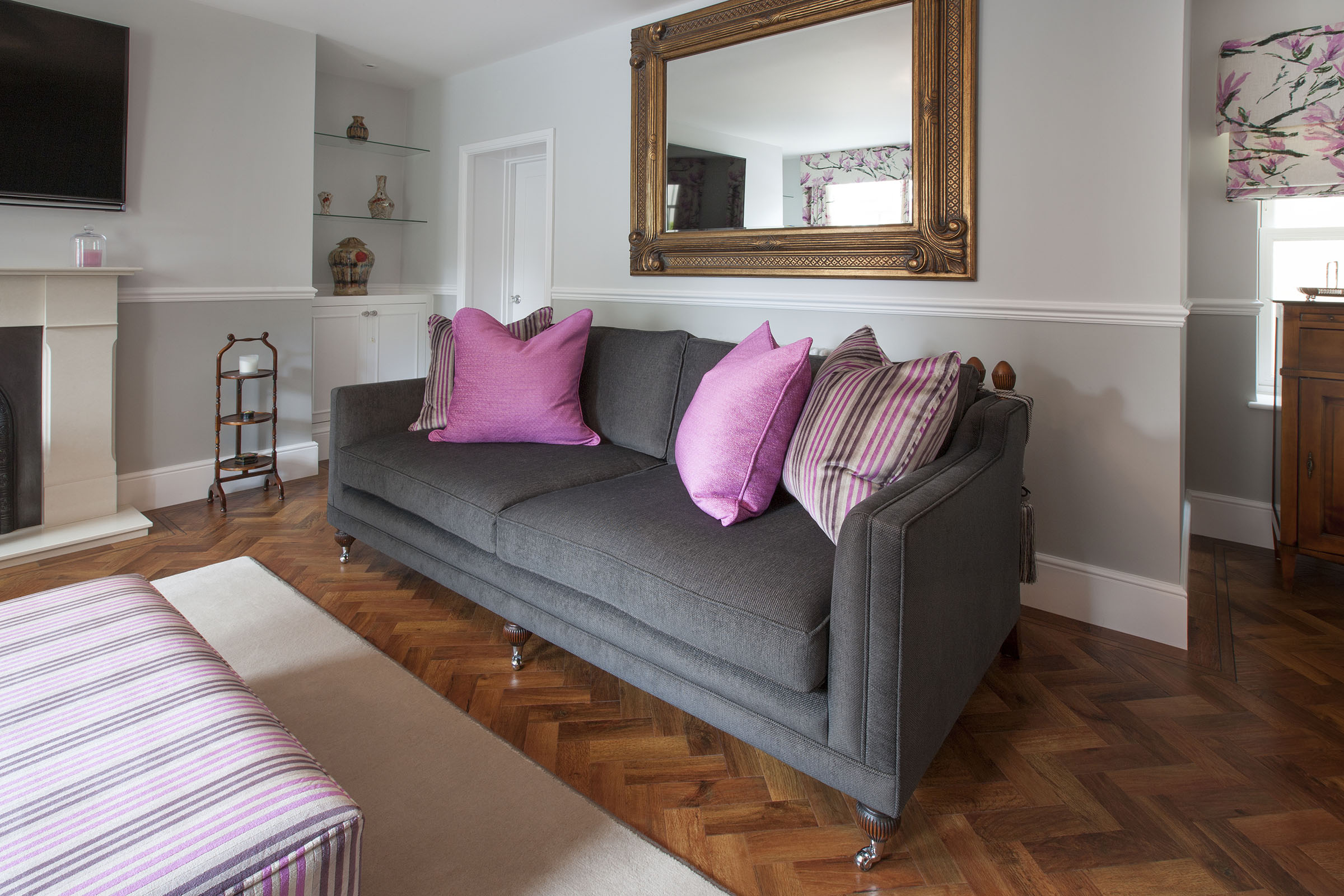 Sitting room with grey and pink theme for sofa, cushions and blinds.