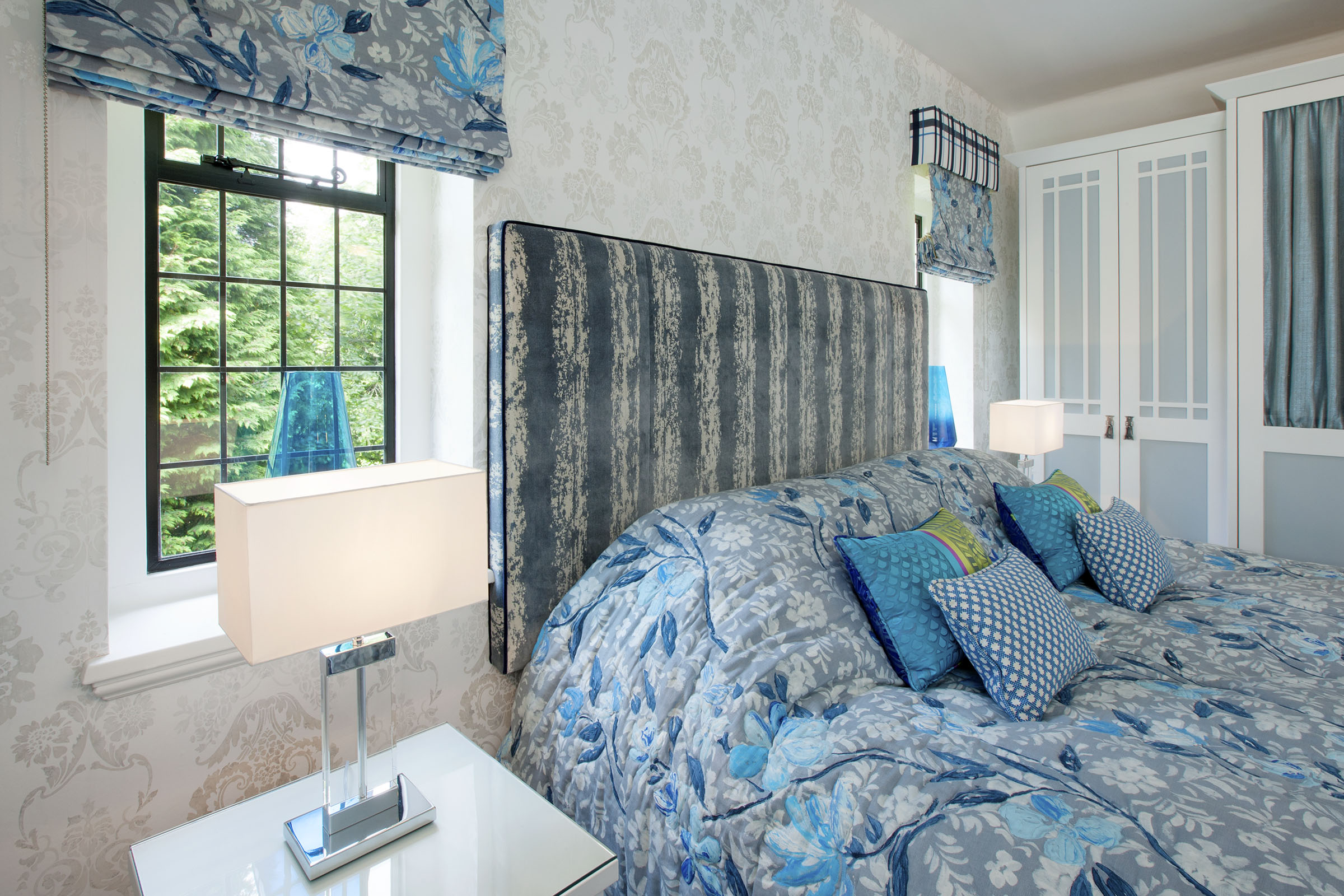 Bedroom with blue and grey co-ordinating duvet cover, headboard, cushions, blinds and curtains.