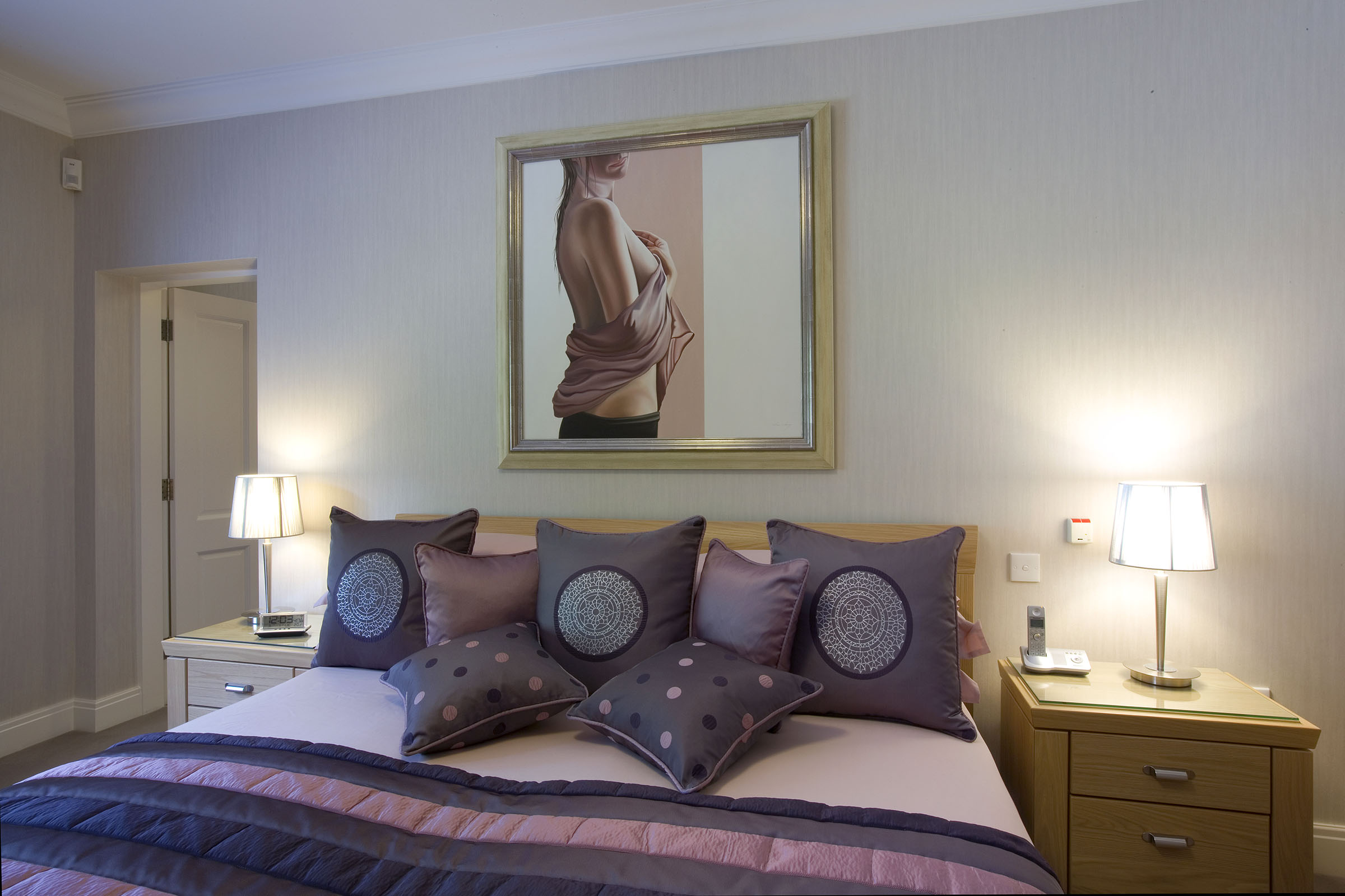 Bedroom with purple and mauve co-ordinating duvet cover and cushions
