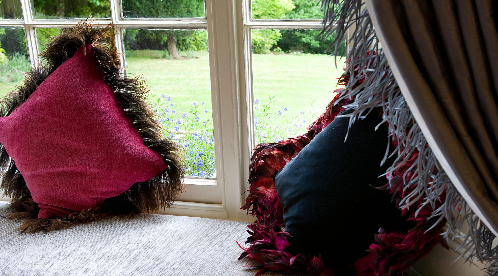 Luxury cushions in window-sill trimmed with faux fur and feathers.