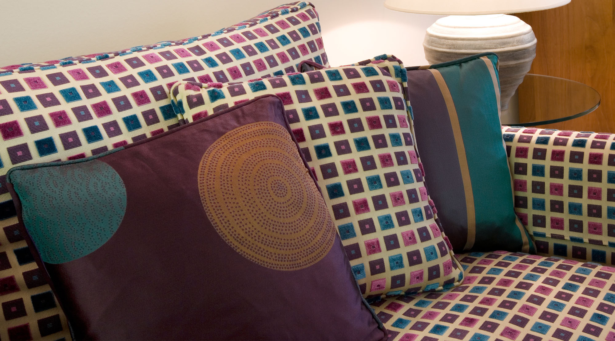 Plum, brown and aqua upholstered sofa with matching and themed cushions.