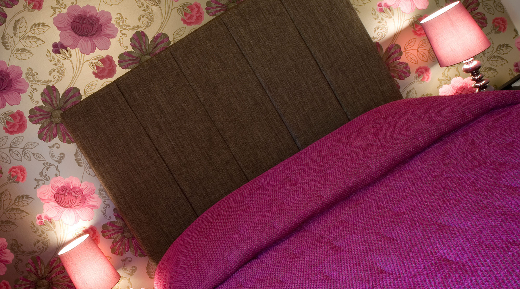 Fushia and brown themed bedroom showing feature wall floral wallpaper, padded headboard and duvet cover.