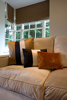 Sitting room in shades of brown and orange. Soft brown sofa, themed cushions and brown Roman blind.